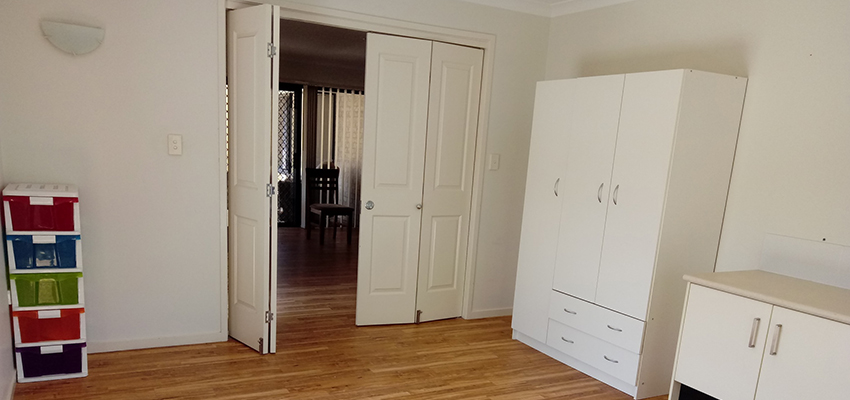 White cabinets, open doorway and brightly coloured drawers in a room with wooden floorboards