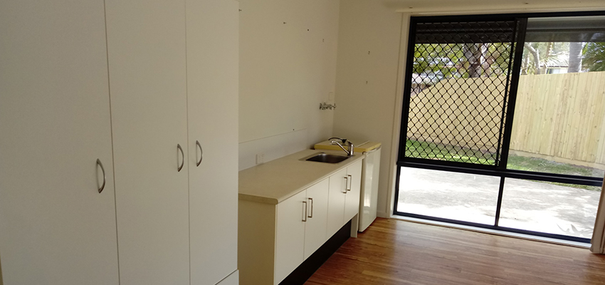 White cabinets and washing machine to the side of a window with security screens