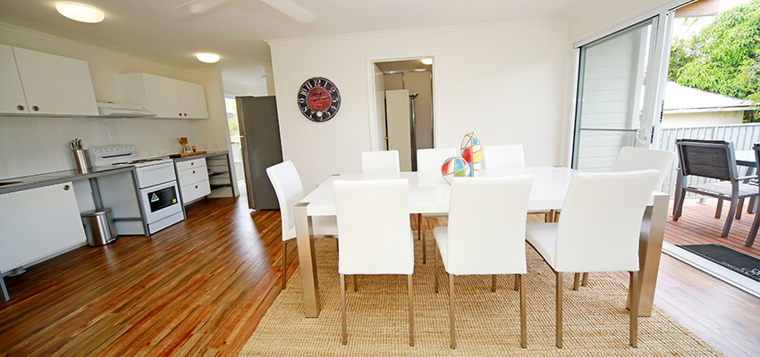 Dining room with white table and chairs on a natural rug and floorboards