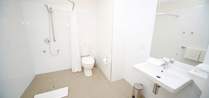 Wet room style bathroom with tiles on floor and walls, toliet, shower and hand basin