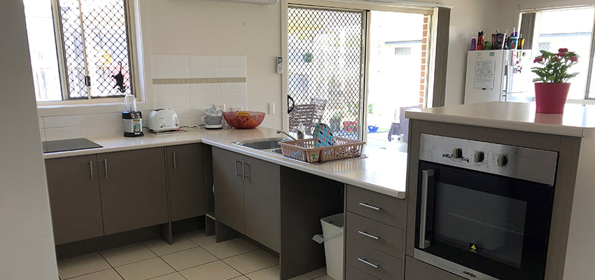 Dark grey kitchen benches and oven with white counter tops