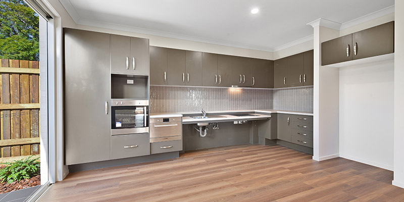 Interior of villa, grey kitchen cabinets and wooden floorboards