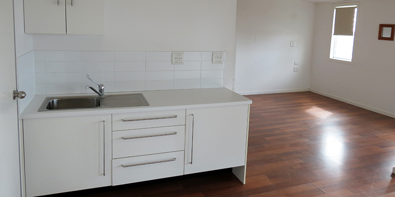 Vacant room with polished wooden floorboards and white kitchenette with sink and cupboards