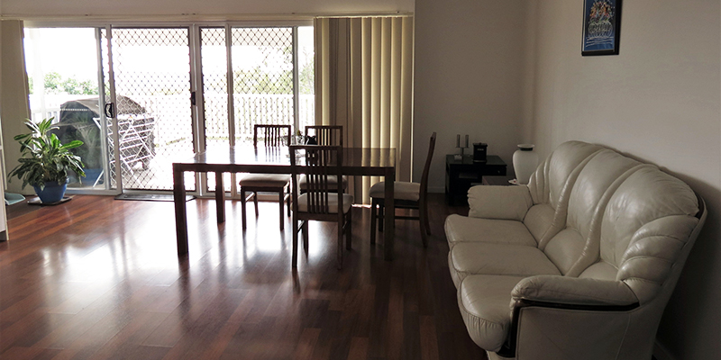 Large living room with polished wooden floorboards. Grey leather couch and dining setting, with sliding doors to deck on back wall.