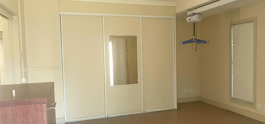 Bedroom with built in wardrobes and mirror. Ceiling hoist and set of drawers also pictured.
