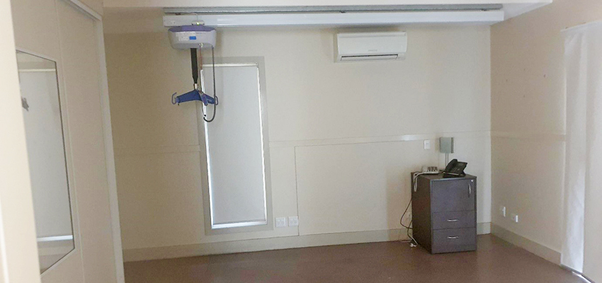 Bedroom with ceiling hoist. There is a small bedside table with a phone on it.