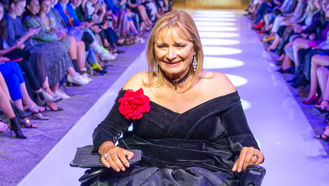 Carol Taylor on the runway at MBFW, woman in a black off-the-shoulder dress in a wheelchair smiling