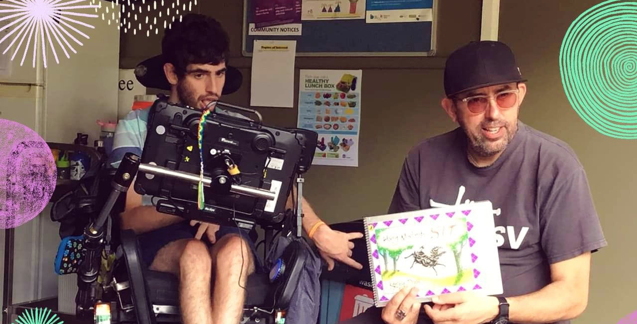 Dale seated in his wheelchair with communication board in front of him, gesturing to a story book being held by his support worker