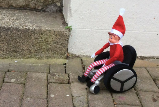 Elf on the shelf toy in a wheelchair, outdoors, paved ground