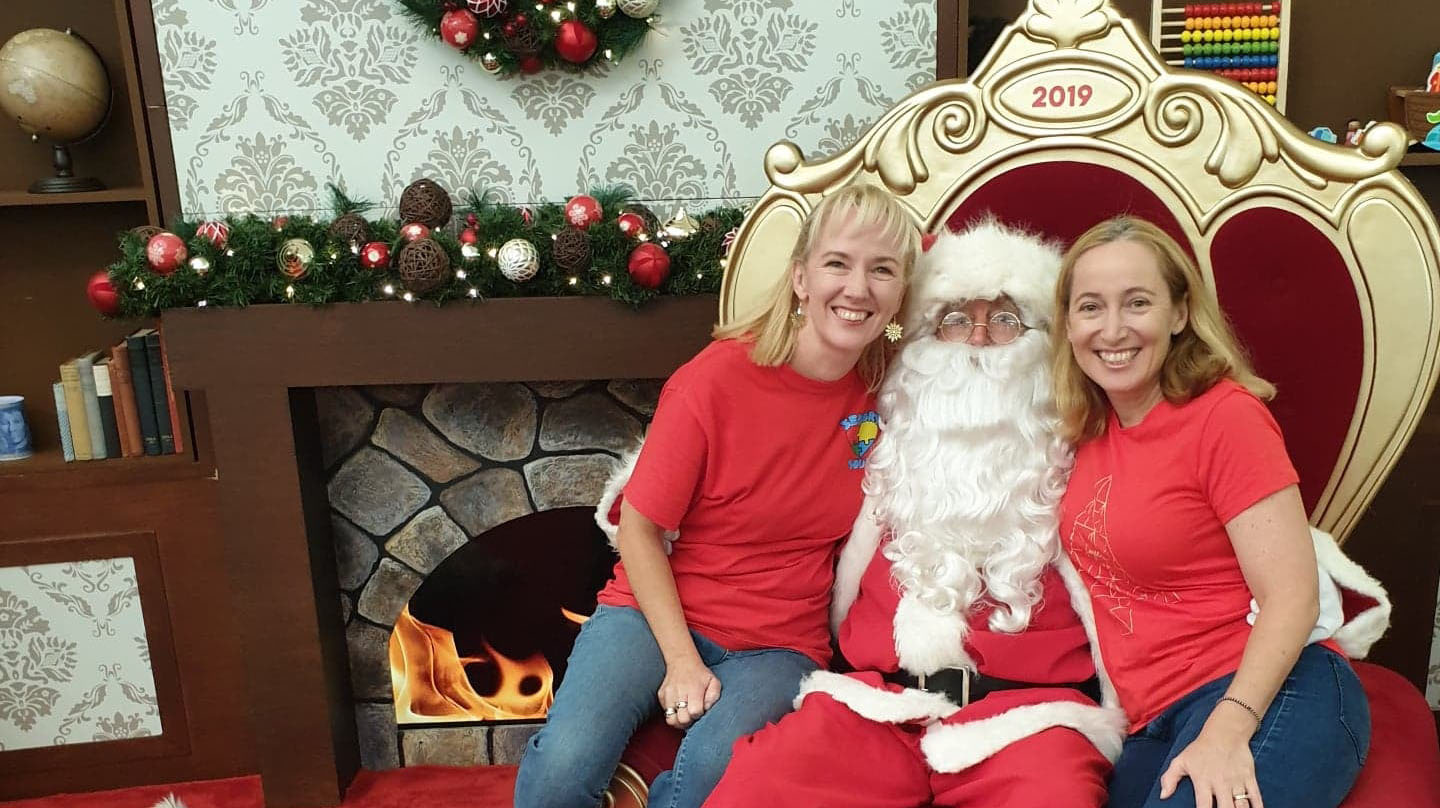 Two women in red t-shirts with Santa