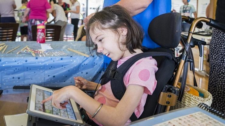 Young girl uses iPad speech device at Camp Have a Chat