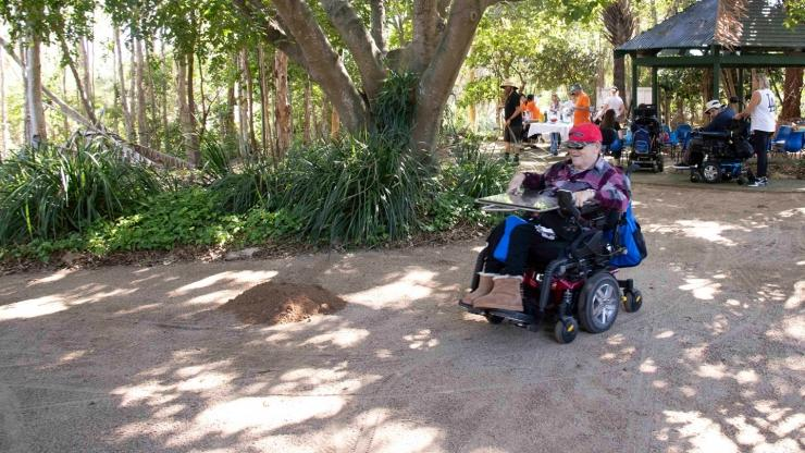 Man in a wheelchair on a garden path, trees, gazebo and other people in the background