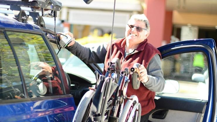Man standing beside a car, moving a wheelchair into the car