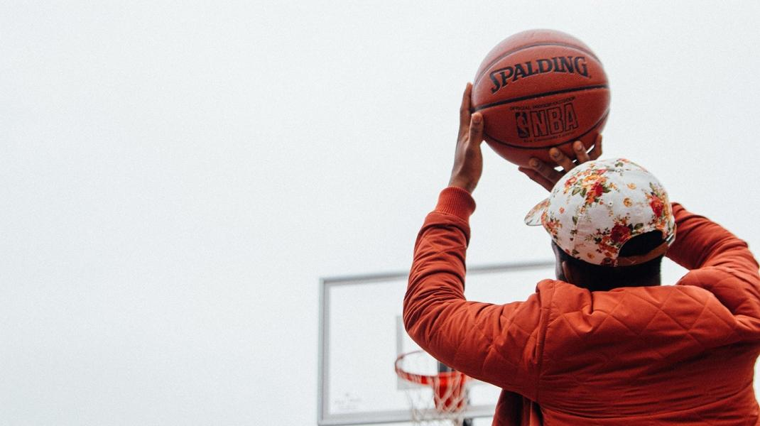Young boy in an orange jacket holds a basketball above his head