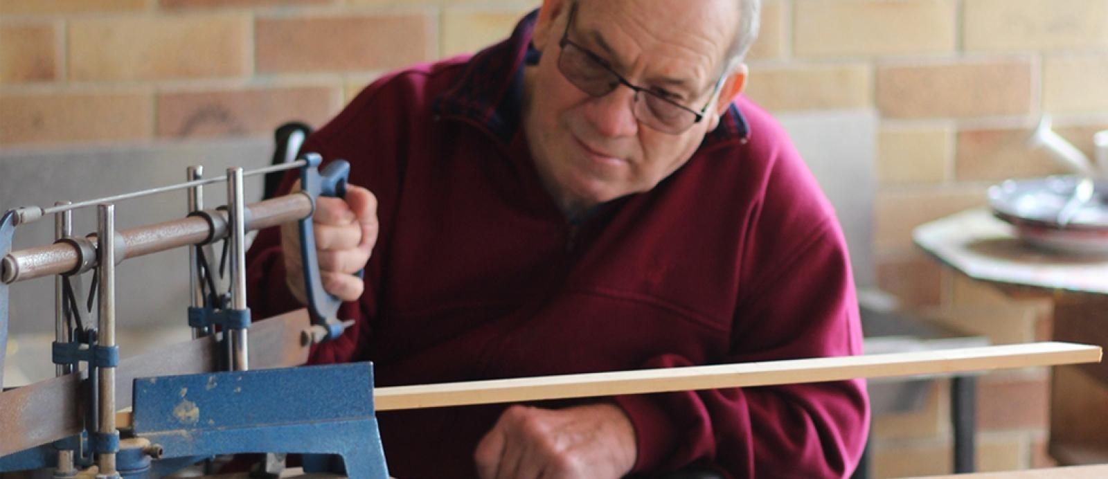 elderly man does woodwork as part of a testimonial about NDIS support coordination